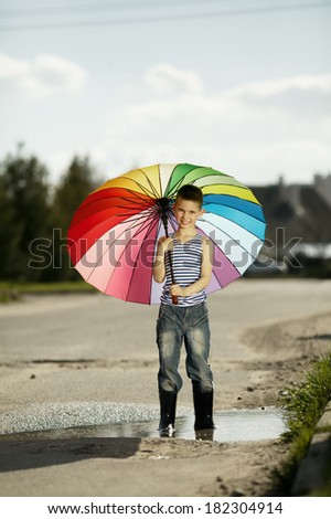 little happy boy with a rainbow umbrella in park