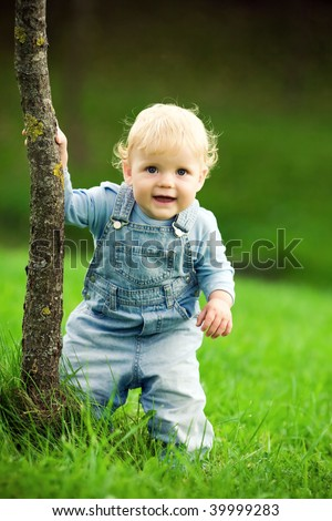 little happy child near the tree