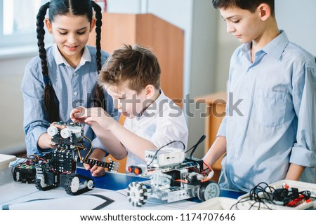 Little happy constructors kids playing with electrical robot while visiting robotics exhibition building a robot, close up of junior technicians being busy with intelligent toys #1174707646