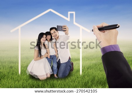 Little happy family taking self photo together on the meadow under a dream home