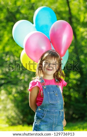 Little happy gir holding colorful balloons