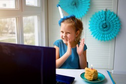 Little happy girl claps her hands, celebrates birthday via the internet in quarantine time, self-isolation and family values, online birthday