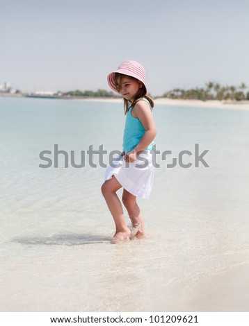 Little happy girl in hat on the beach