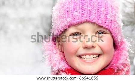 Little happy girl in winter pink hat in snow forest.