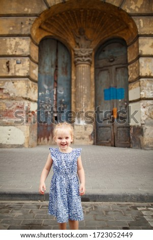 little happy girl kid is laughing in the background of an old door in an abandoned house