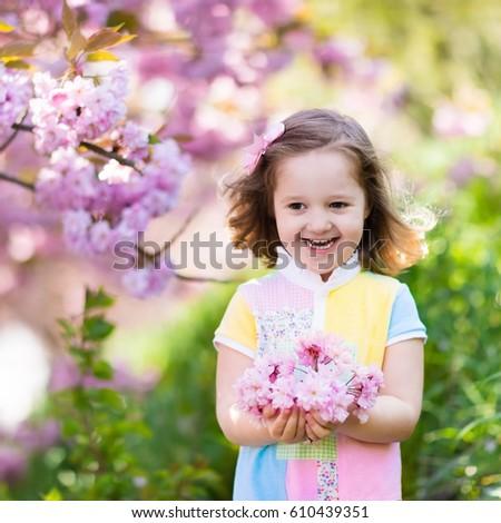 Little happy girl playing under blooming cherry tree with pink little happy girl playing under blooming cherry tree with pink flowers child holding sakura blossom mightylinksfo