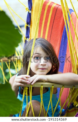 Little happy girl relaxing in hammock