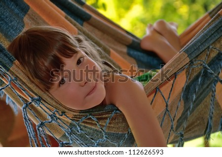 Little happy girl relaxing in hammock. Smiling kid on family summer vacation