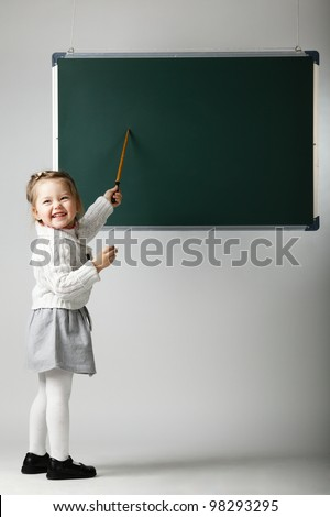 little happy girl with pointer standing near the blackboard