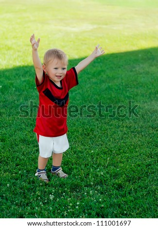 Little happy soccer player rejoices after score goal