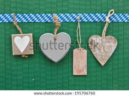 Little heart-shaped tags on green wooden background