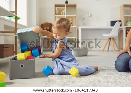 Little helper cleaning up and learning to be independent. Cute 2 year old child putting cubes back in their place after playing. Toddler boy putting toys away sitting on warm floor in nursery room Foto d'archivio ©