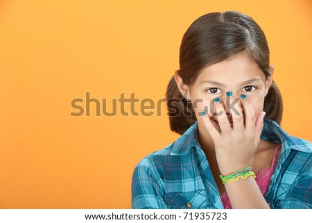 Little Hispanic girl covers a smile with her hand