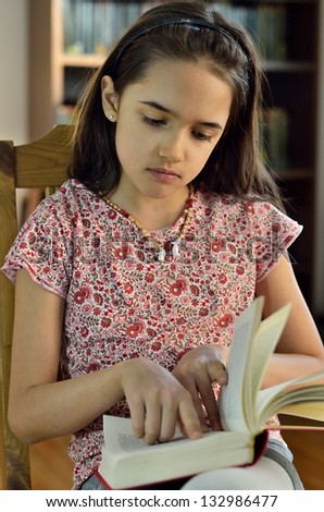 Little Hispanic Girl Reads a Book - stock photo