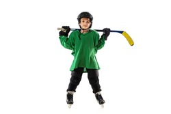 Little hockey player with the stick on ice court, white studio background. Sportsboy wearing equipment and helmet, practicing, training. Concept of sport, healthy lifestyle, motion, movement, action.