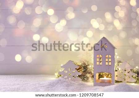 Little house candle holder xmas decorations on snow with fairy light holidays card template #1209708547