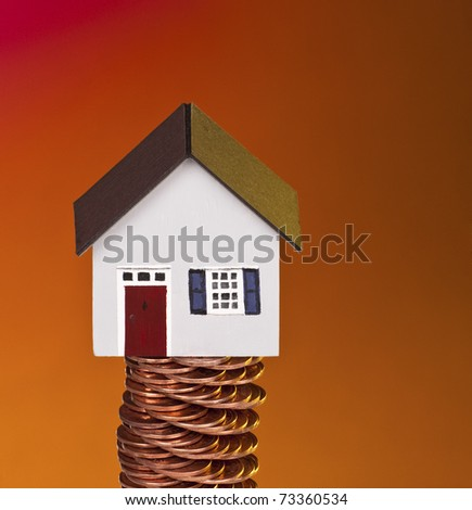 Little house on old stacked coins. Mortgage or equity concept with copy space.
