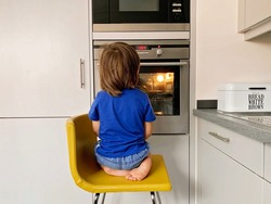 Little hungry toddler boy sitting at oven looking inside through the glass waiting for pizza.