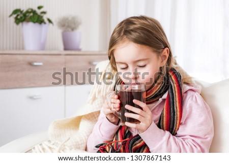 Little ill girl in scarf drinking tea