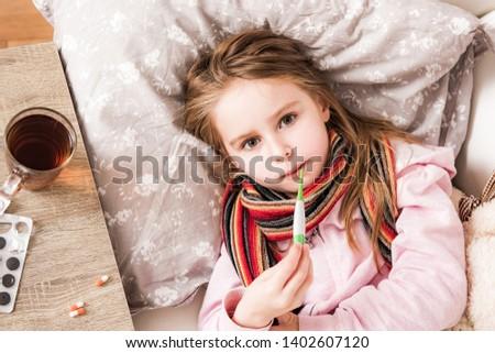 Little ill girl measuring temperature
