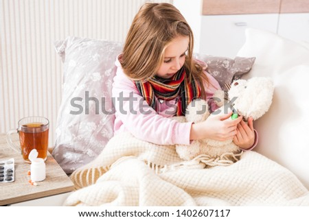 Little ill girl treating and measuring teddy bear's temperature