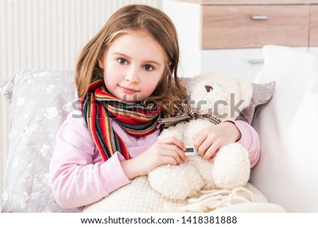 Little ill girl with scarf measuring teddy bear's temperature