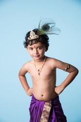 Little Indian boy posing as Shri krishna or kanha/kanhaiya on fancy dress or Gokulashtami festival. isolated over colourful background
