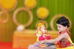 Little Indian child with lord ganesha and praying , Indian ganesh festival