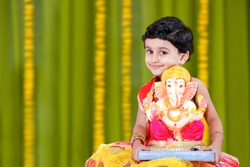 Little Indian girl child with lord ganesha and praying , Indian ganesh festival