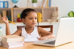 Little Indian girl looking at the laptop while doing homework
