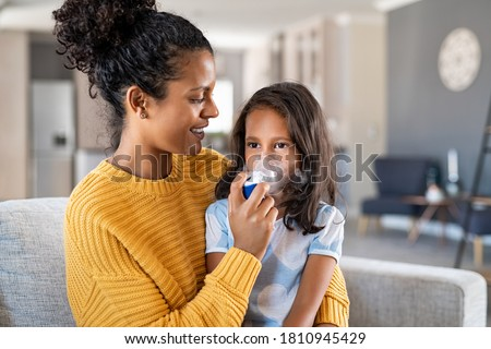 Little indian girl making inhalation with nebulizer with lovely mother. Woman makes inhalation to a sick child while embracing her. Mom helping daughter with cold and flu to inahale nebuliser aerosol. Foto stock ©