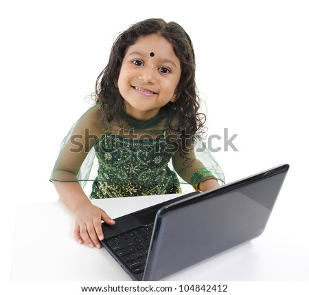 Indian girl using a laptop on table, isolated on white background ...