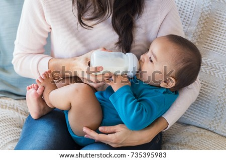 Little infant baby lying on mothers hand drinking milk from bottle. Hispanic loving mother feed her cute toddler while sitting on sofa.