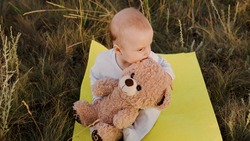Little Infant, boy hugs his favorite soft teddy bear on playground. Child girl playing with teddy bear. Plush toy in hands of kid in summer park. Kid plays with toy, dreams in fresh air. Best friends