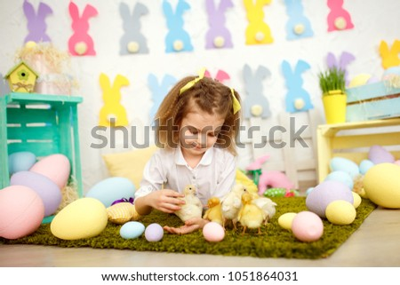 Little innocent girl in bows lying on green lawn with eggs and playing with yellow small ducklings and chikens in Easter decoration. #1051864031