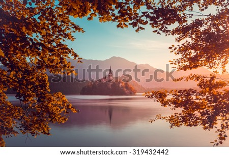 Little Island with Catholic Church in Bled Lake, Slovenia  at Sunrise with Castle and Mountains in Background. Autumn Filter. Tree Leaves Border. Natural Frame.