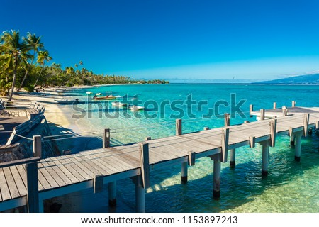 Little jetty and boat on tropical beach with amazing water, Moorea, Tahiti #1153897243