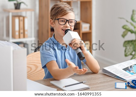 Little journalist with microphone having an interview in office