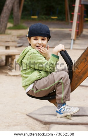 Little joyful boy shaking on a swing on adventure playground