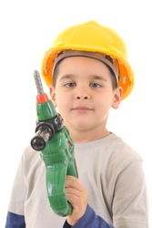 Little kid as a construction worker wearing yellow helmet holding drill like a gun.White background vertical studio picture.