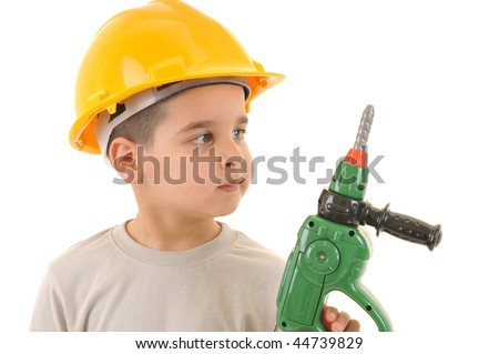 Little kid as a construction worker wearing yellow helmet holding drill like a gun.White background studio picture.