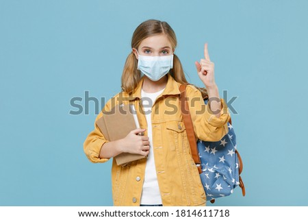 Little kid blonde girl 12-13 years old with backpack sterile face mask to safe from coronavirus virus covid-19 during pandemic quarantine hold school books point finger up isolated on blue background. Stock photo ©