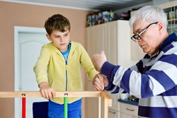 Little kid boy and grandfather working and constructing and repairing together. Senior man works with screwdriver and cute grandson learning. Happy family having fun together, granddad and child