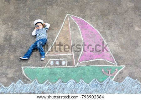 Little kid boy as pirate on ship or sailingboat picture painting with colorful chalks on asphalt. Creative leisure for children outdoors in summer. Child with captain hat and binoculars