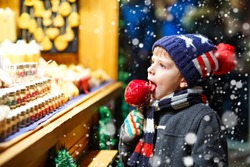 Little kid boy eating sugar apple sweets stand on Christmas market