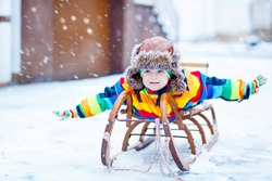 Little kid boy riding and sitting on a vintage sledge in snowy park. School child playing outdoors and have fun in winter during snowfall.