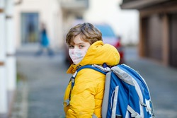 Little kid boy wearing medical mask on the way to school. Child backpack satchel. Schoolkid on winter day with warm clothes. Lockdown and quarantine time during corona pandemic disease