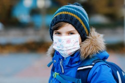 Little kid boy wearing medical mask on the way to school. Child backpack satchel. Schoolkid on cold autumn or winter day with warm clothes. Lockdown and quarantine time during corona pandemic disease
