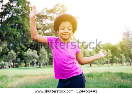 Little kid dancing and listening to music in green park #524461441