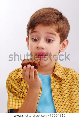 Little kid eating a chocolate brownie on white background.